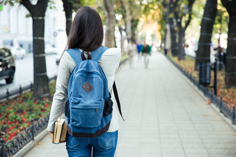 carteira de estudante falsa. na imagem, mulher de cabelos cumpridos de costas e com mochila azul